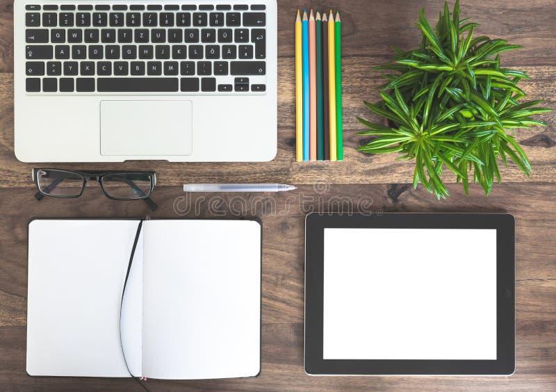 Libreta, ordenador portátil, planta verde y tableta en el escritorio de madera fotos de archivo libres de regalías