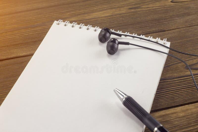 Libreta, pluma, auriculares en una educación de madera del fondo imágenes de archivo libres de regalías