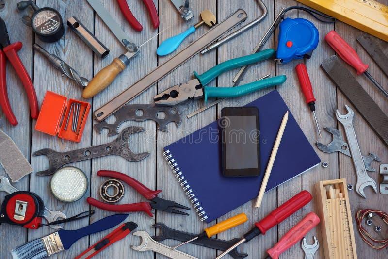 Libreta, teléfono móvil y herramientas en un piso de madera, visión superior imagen de archivo libre de regalías