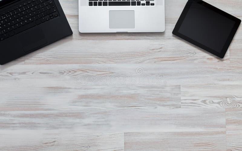 Libreta y ordenador portátil en la tabla de madera Visión desde arriba imagenes de archivo