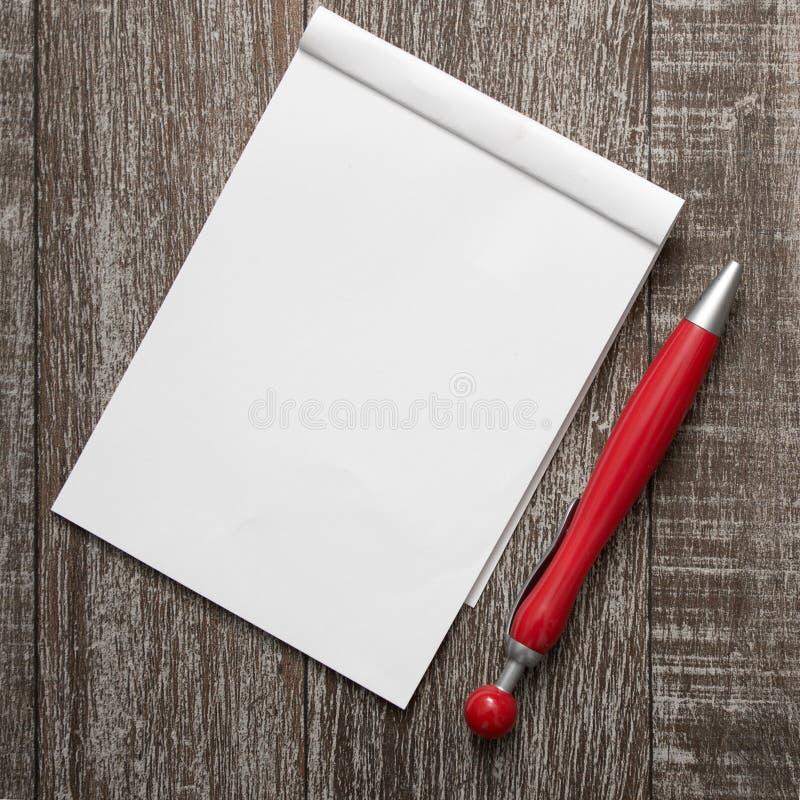 Libreta y pluma en blanco en la tabla de madera fotografía de archivo