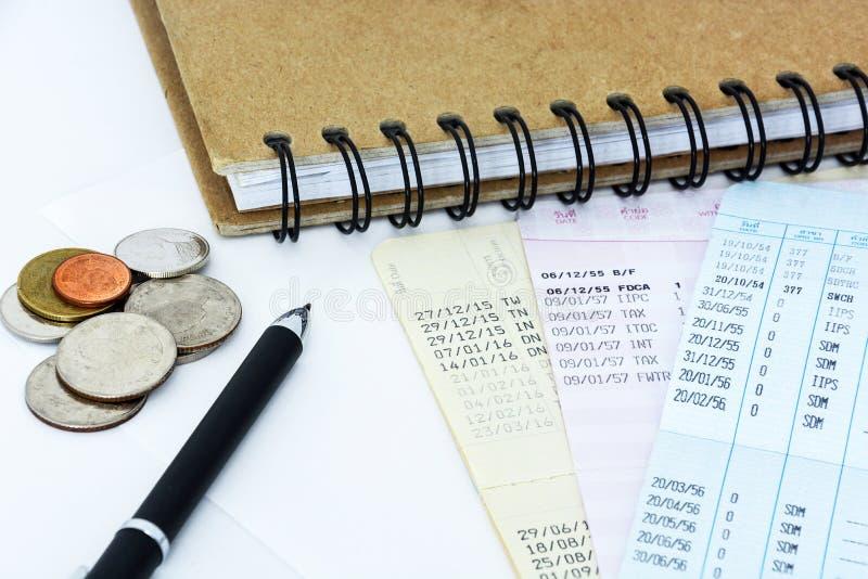 Libretas de banco y monedas de cuenta de ahorro con la pluma y el cuaderno en el fondo blanco imagen de archivo
