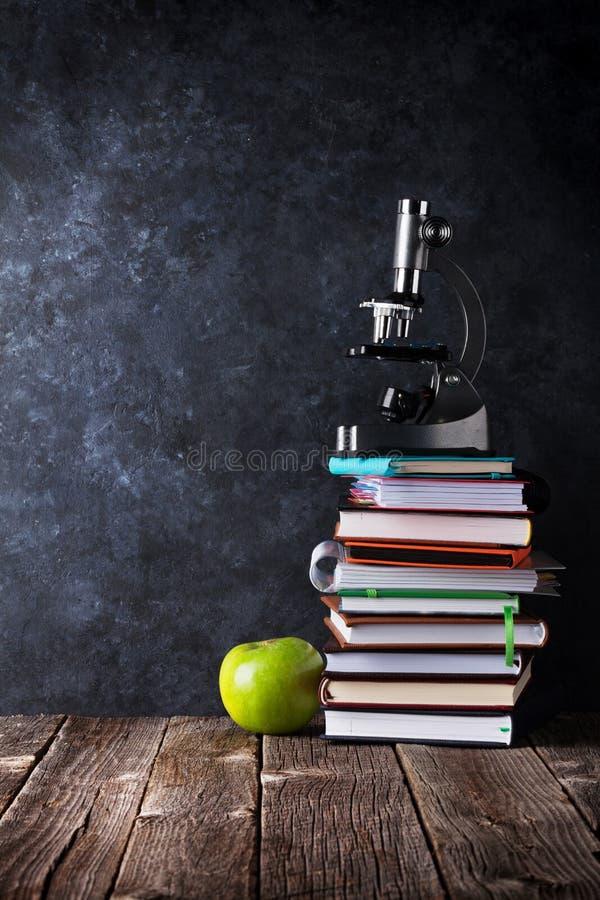 Libretas, microscopio y manzana delante del tablero de tiza imágenes de archivo libres de regalías