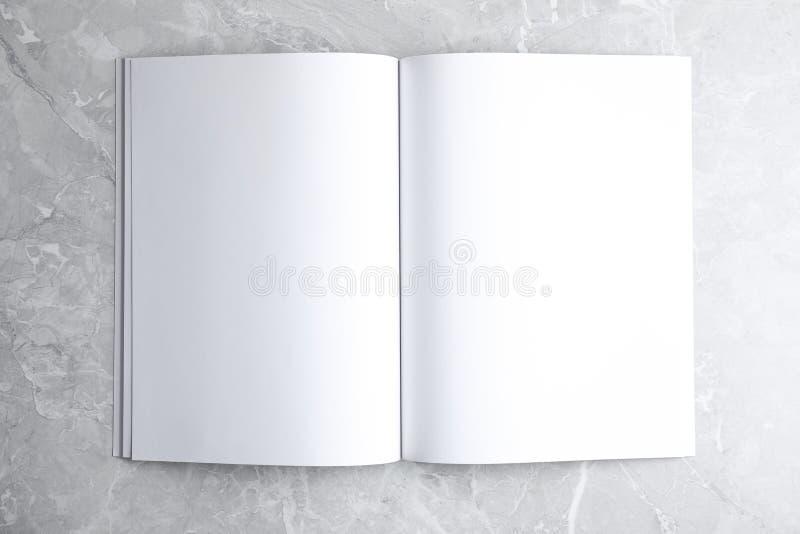 Libretto aperto vuoto su fondo di marmo grigio chiaro, vista superiore Ingrandisci il design fotografia stock