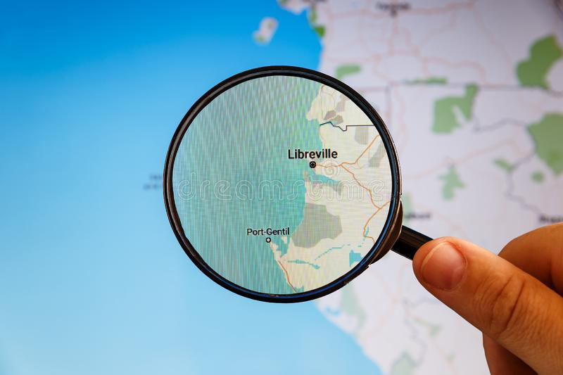 Libreville, Gabon. Political map. City visualization illustrative concept on display screen through magnifying glass in the hand royalty free stock image