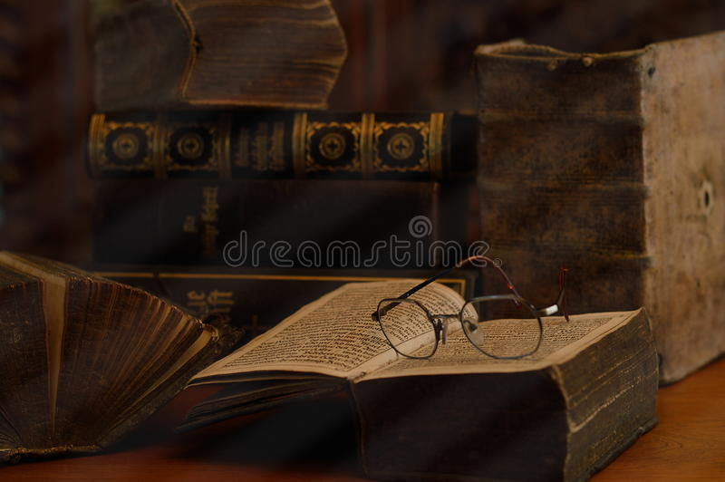 Libri antichi con i vetri di lettura in una stanza polverosa immagini stock libere da diritti