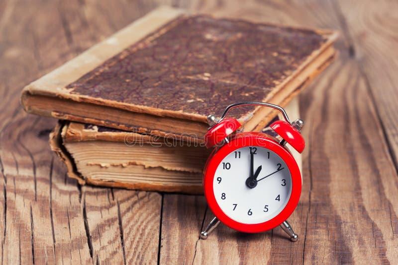 Libri d'annata e una sveglia immagine stock