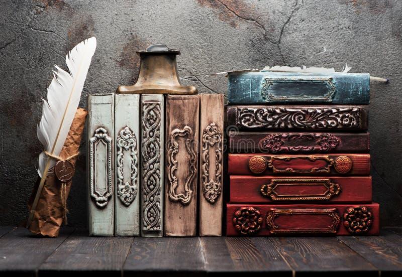 Libri d'annata su uno scaffale di legno, su un rotolo di carta con una guarnizione della cera, su uno iinkwell e su una piuma per immagini stock