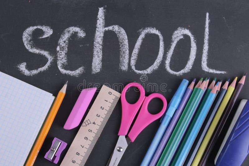 Libri dei rifornimenti di scuola, astuccio per le matite, matite in un vetro e un taccuino sui precedenti di un consiglio scolast immagini stock