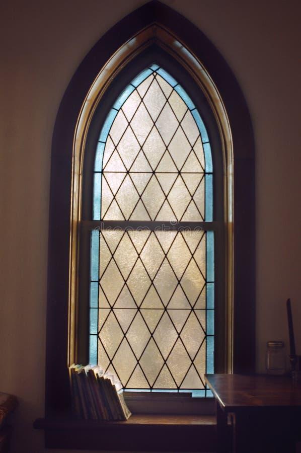 Libri della finestra della chiesa del vetro macchiato fotografia stock