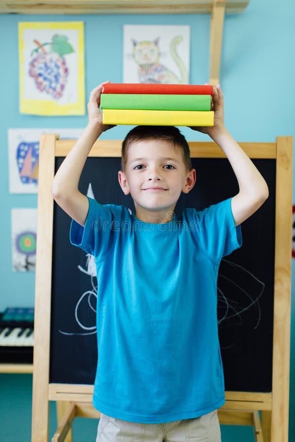 Libri di equilibratura del ragazzo di scuola sul suo testa immagini stock libere da diritti