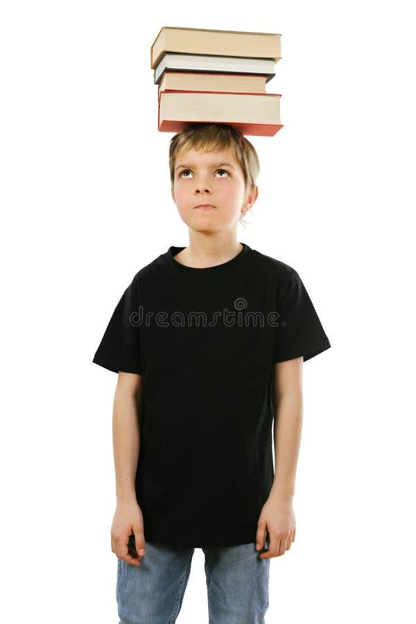 Libri di equilibratura del ragazzo sul suo testa fotografie stock