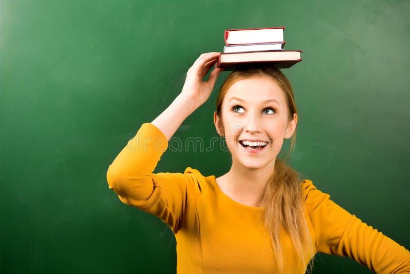 Libri di equilibratura della donna sulla testa fotografie stock