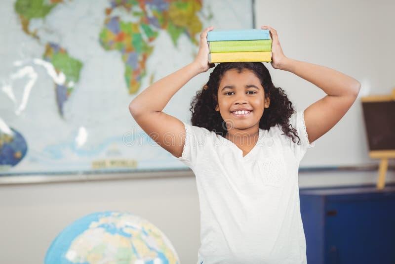 Libri di equilibratura sorridenti dell'allievo sulla testa in un'aula fotografie stock