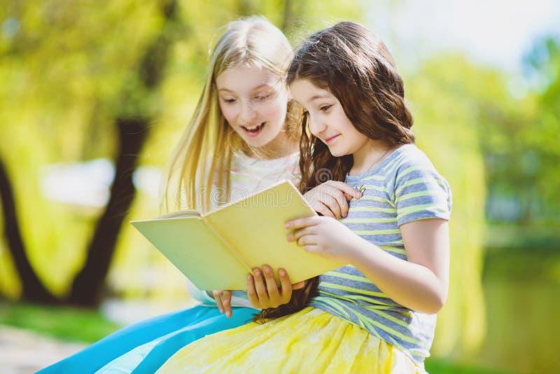 Libri di lettura dei bambini al parco Ragazze che si siedono contro gli alberi e lago all'aperto fotografia stock