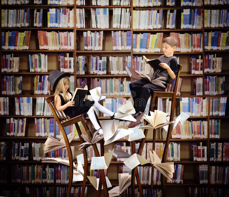 Libri di lettura dei bambini nella biblioteca di fantasia immagine stock