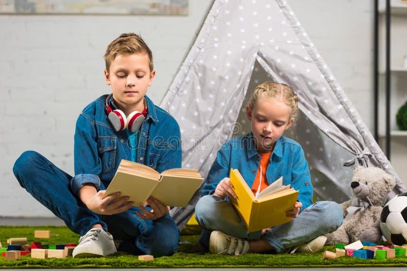 libri di lettura messi a fuoco del fratello e della sorellina vicino alla tenda immagine stock