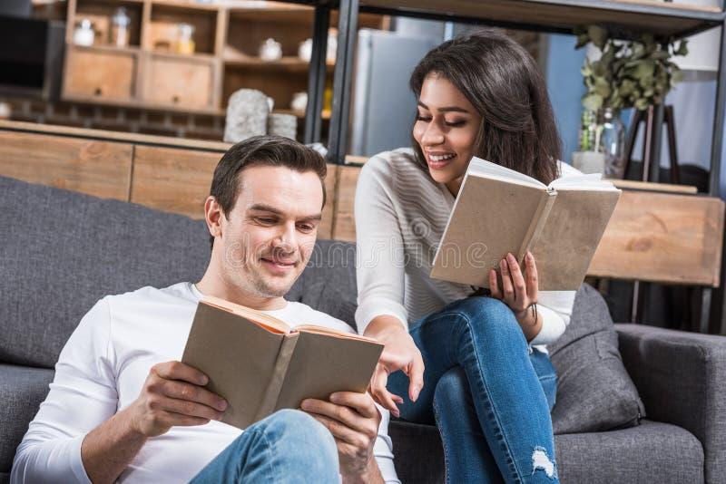 libri di lettura multietnici felici delle coppie insieme fotografie stock
