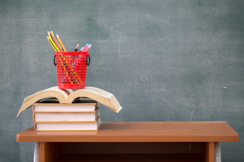 Libri di scuola sullo scrittorio, libri e lavagna su fondo di legno, concetto di istruzione fotografie stock libere da diritti