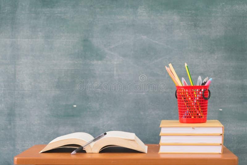 Libri di scuola sullo scrittorio, di nuovo ai rifornimenti di scuola Libri e lavagna su fondo di legno, concetto di istruzione fotografia stock libera da diritti