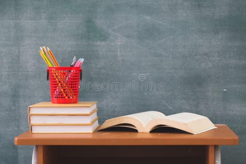 Libri di scuola sullo scrittorio, di nuovo ai rifornimenti di scuola Libri e lavagna su fondo di legno, concetto di istruzione fotografie stock libere da diritti