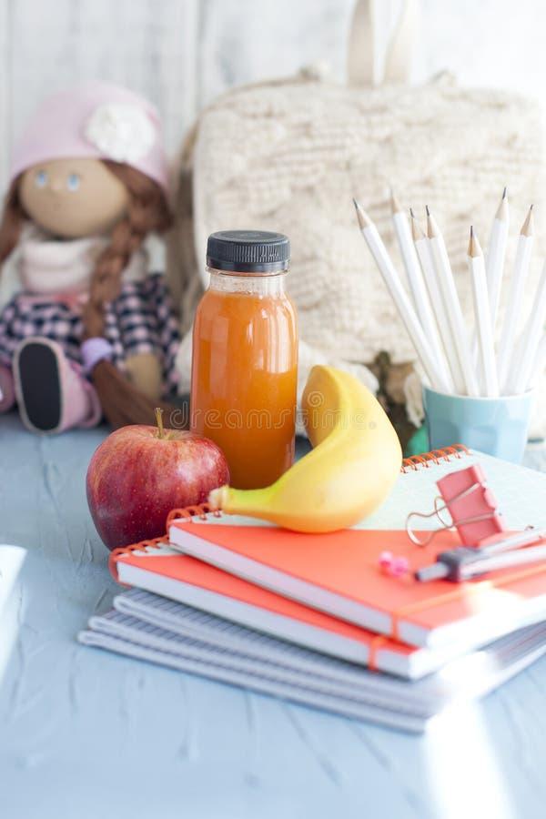 Libri di scuola, sveglia, bambola e fondo per testo fotografia stock