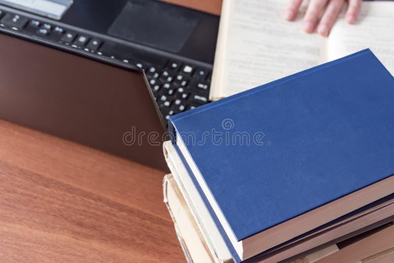 Libri e computer portatile sul desktop La mano si trova sul libro fotografia stock