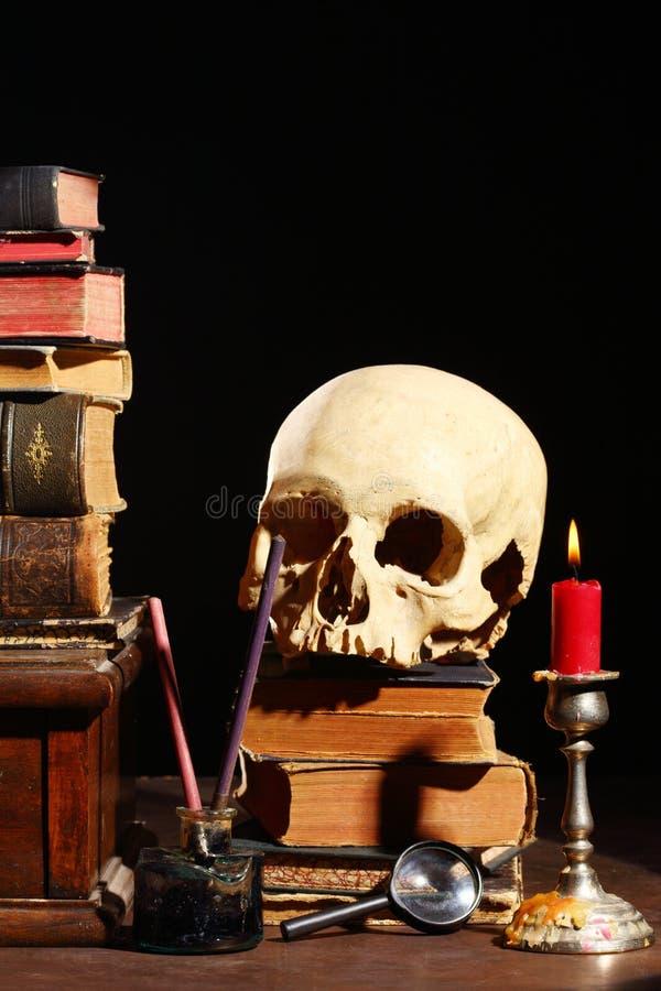 Libri e cranio fotografie stock