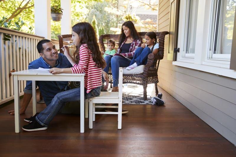 Libri e giocare di lettura di Sit On Porch Of House della famiglia immagini stock