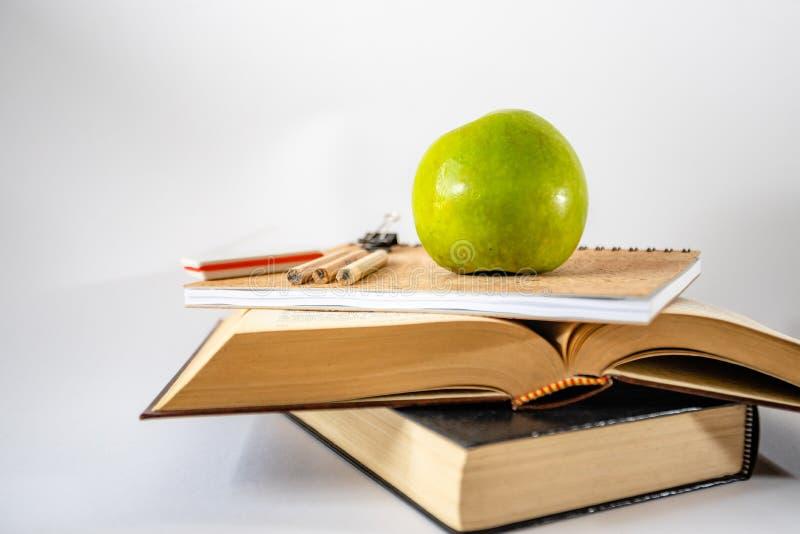 Libri e mela su priorità bassa bianca fotografie stock libere da diritti