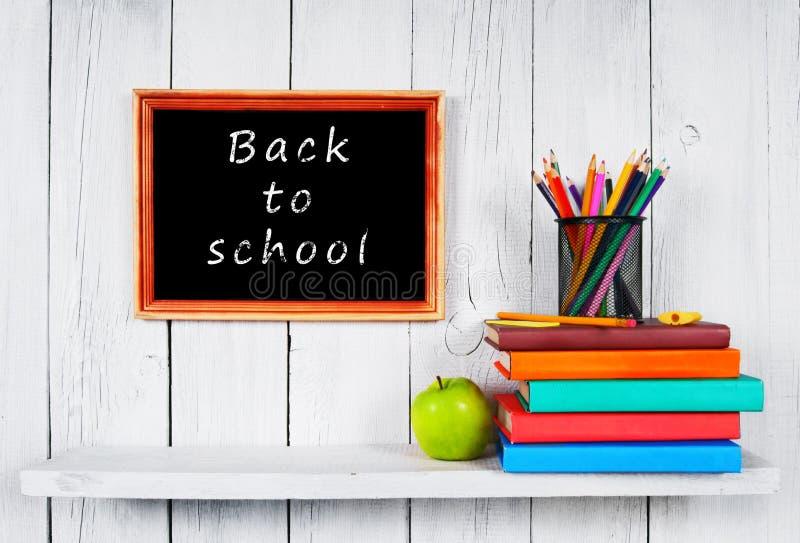 Libri e strumenti della scuola sullo scaffale di legno fotografia stock