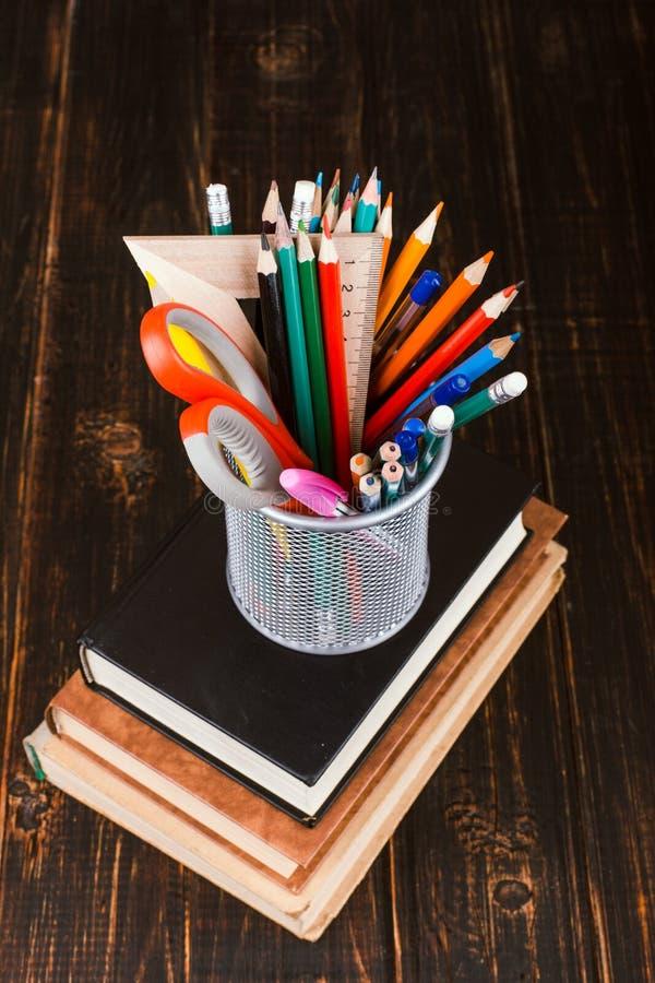 Libri e supporto per le penne su una tavola di legno Teacher& x27; concetto di giorno di s e di nuovo a scuola fotografia stock libera da diritti