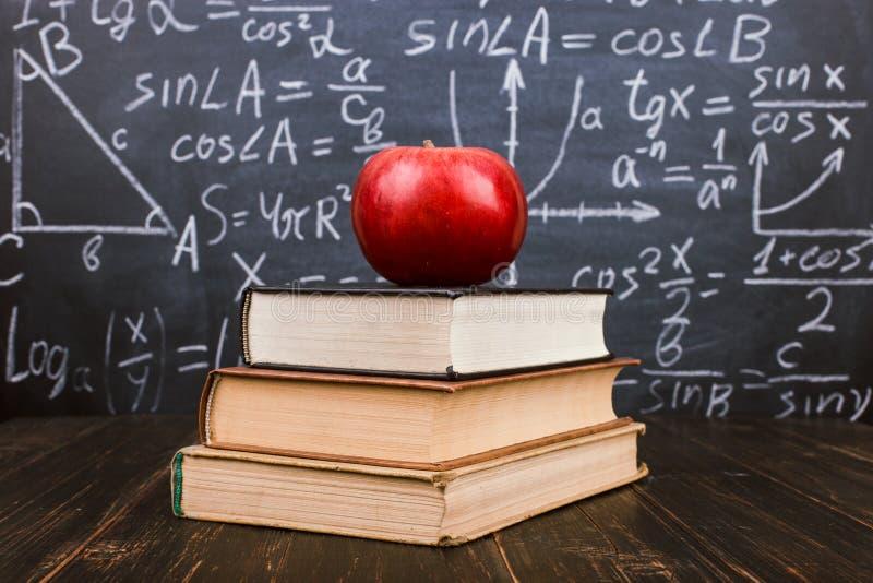 Libri e una mela su una tavola di legno, contro lo sfondo di una lavagna con le formule Teacher& x27; concetto di giorno di s e d immagine stock libera da diritti