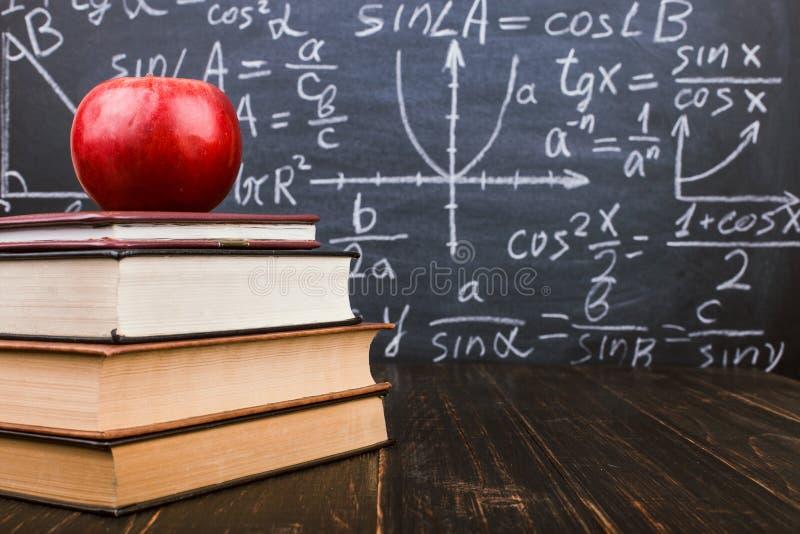 Libri e una mela su una tavola di legno, contro lo sfondo di una lavagna con le formule Teacher' concetto di giorno di s e d fotografie stock libere da diritti