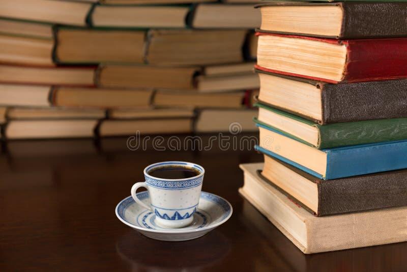 Libri e una tazza di caffè sulla tavola fotografia stock