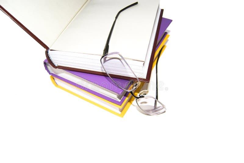 Libri e vetro colorati su una priorità bassa bianca. fotografia stock libera da diritti