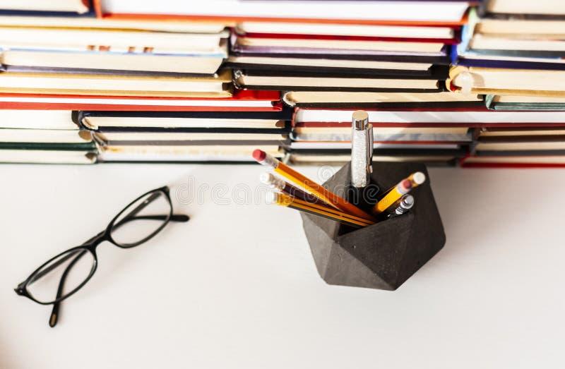 Libri fondo, vetri, penne e matite sulla tavola di legno bianca fotografia stock