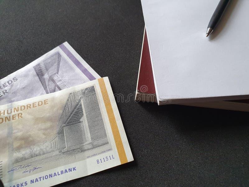 libri impilati, penna nera e soldi danesi sulla tavola nera immagine stock libera da diritti