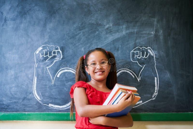 Libri ispani della tenuta della ragazza in aula e nel sorridere fotografia stock