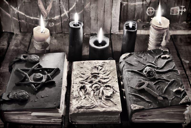 Libri magici della strega con le candele brucianti della cera e del nero nell'oscurità immagine stock