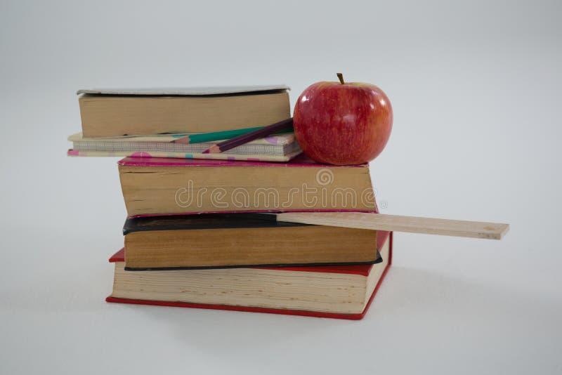 Libri, matite di colore, scala e mela su fondo bianco immagine stock