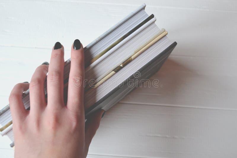 Libri nella mano della donna sui precedenti bianchi fotografia stock libera da diritti