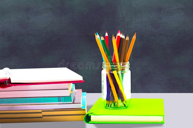 Libri, penna, matita e mobili d'ufficio su fondo blu, istruzione e di nuovo alla materia d'insegnamento, percorso di ritaglio fotografie stock libere da diritti