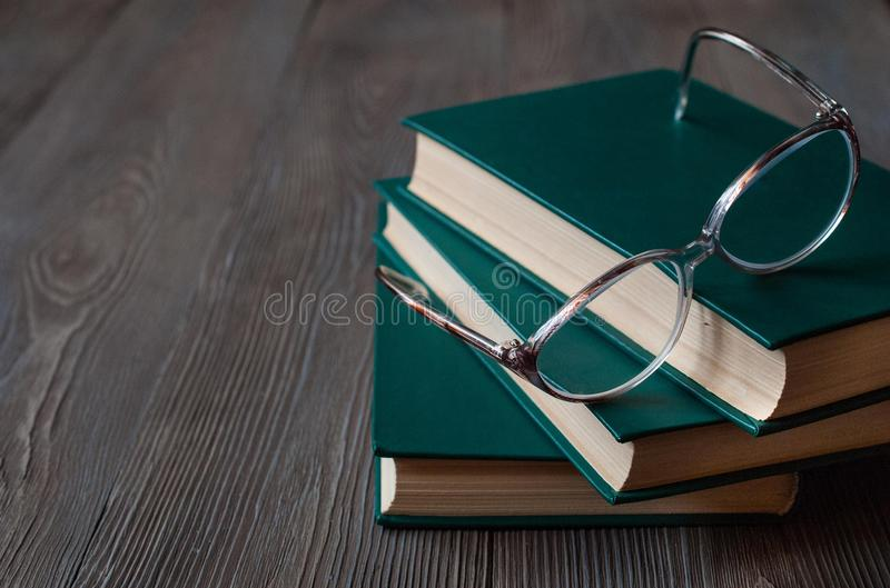Libri per la lettura su un fondo scuro, vetri di lettura fotografia stock
