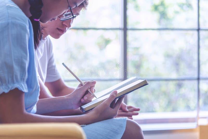 Libri stressanti di ripetizioni e di lettura di due dell'adolescente studenti della città universitaria insieme Gli amici discute immagini stock