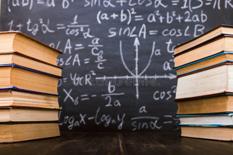 Libri su una tavola di legno, contro lo sfondo di un bordo di gesso con le formule Teacher' concetto di giorno di s e di nuo fotografia stock libera da diritti