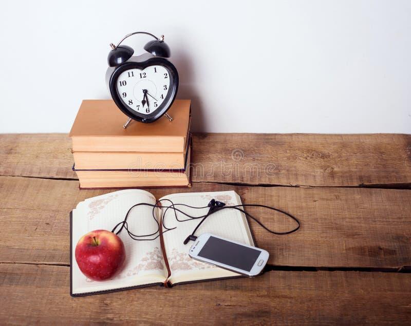 Libri, sveglia, blocco note, cellulare e mela su fondo di legno immagine stock libera da diritti