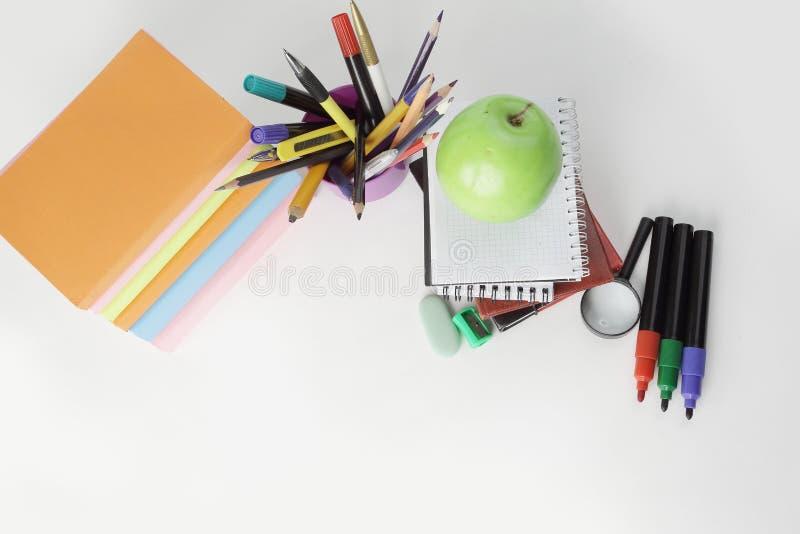 Libri, taccuini e rifornimenti di scuola su fondo bianco Concetto di formazione immagini stock libere da diritti