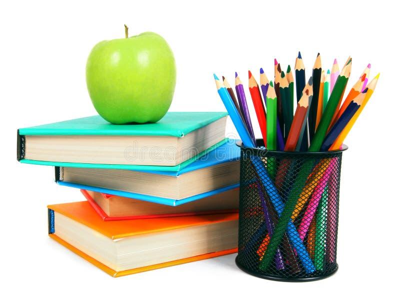 Libri, una mela e matite Su fondo bianco immagine stock