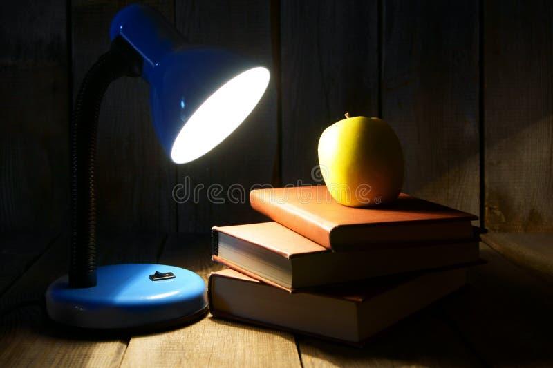 Libri, una mela ed il dispositivo fotografie stock libere da diritti